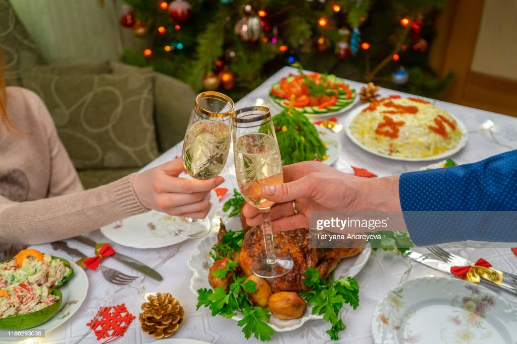 Human hands holding glasses with sparkling wine. Friends or family toasting with champagne against festive Christmas table and decorated new year tree. Winter holidays celebration at cozy home : Stock Photo