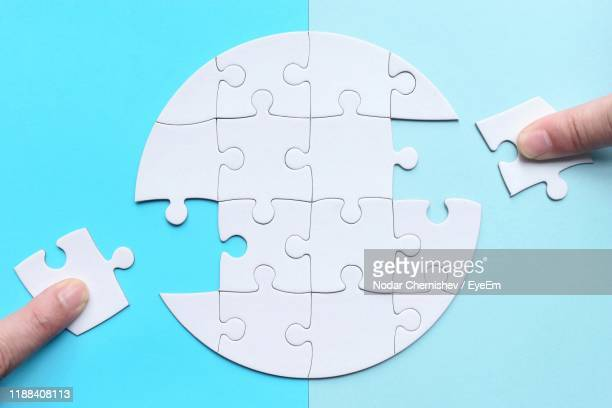 human hands holding jigsaw pieces - jigsaw piece stock pictures, royalty-free photos & images