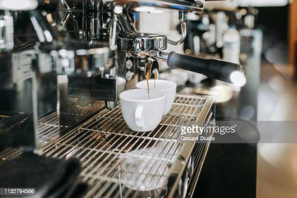 human hands making fresh espresso coffee drink - coffee maker stock pictures, royalty-free photos & images