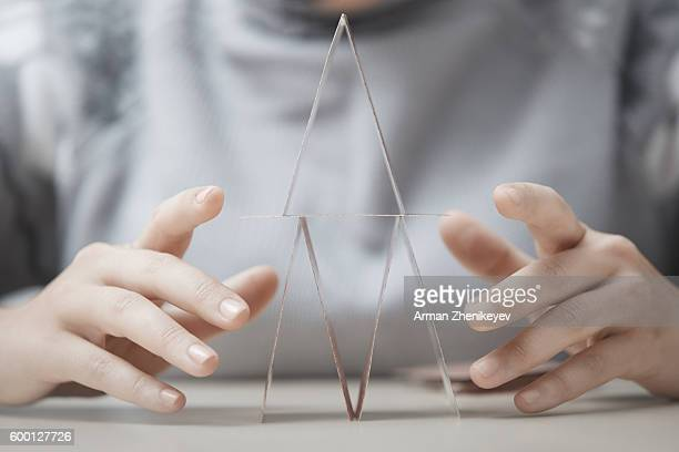 Human hands making house of cards
