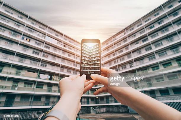 Human hands photographing old residential estate and a rising sun with smartphone in Hong Kong.