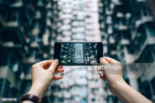 human hands photographing the facade of old and high density residential blocks with smartphone in city - skyscraper film stock pictures, royalty-free photos & images