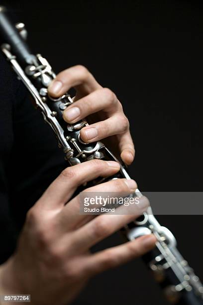 Human hands playing a clarinet