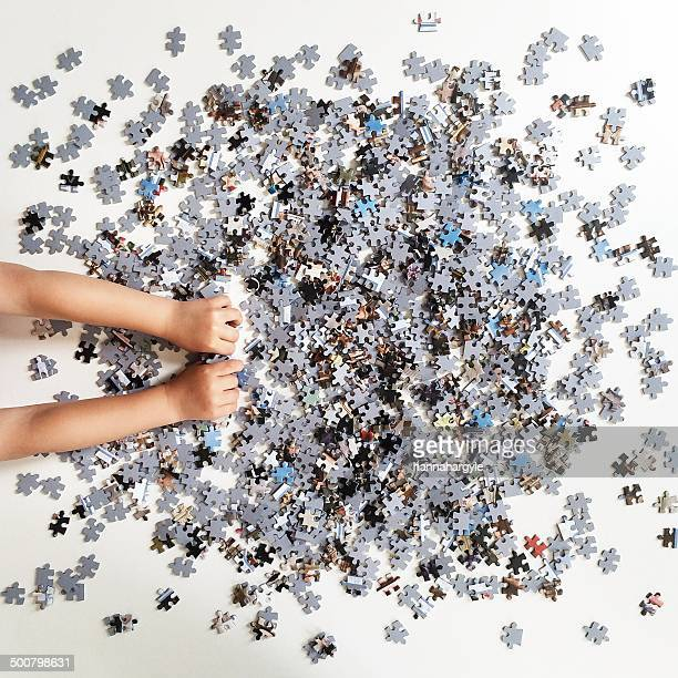 Human hands playing with jigsaw puzzle pieces