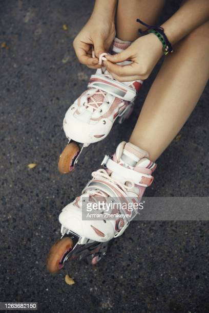 human hands putting on and lacing roller skates - lace fastener stock pictures, royalty-free photos & images