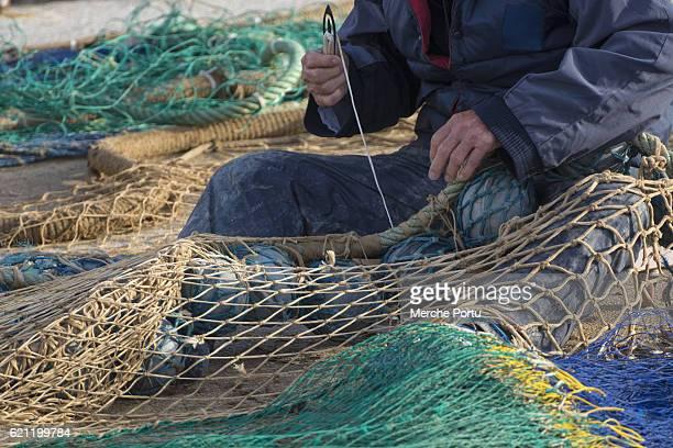 Human hands sewing fishing nets