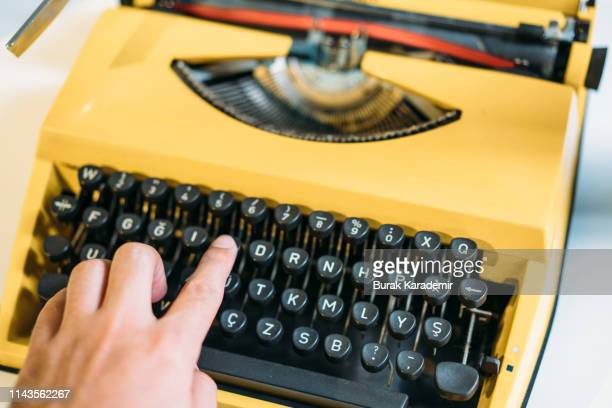 human hands typing on yellow vintage type writer machine - storyteller stock pictures, royalty-free photos & images