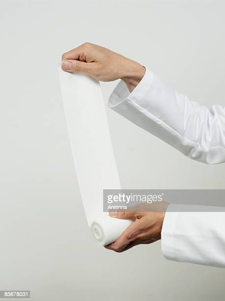 Human hands unrolling a strip of gauze