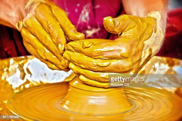 Human hands working on a potters wheel