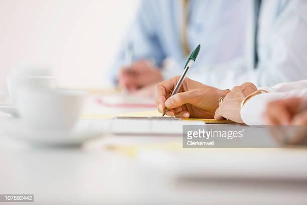 Homme mains par écrit sur le carnet à la table de conférence