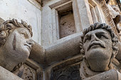 Human heads on the side portal of The Cathedral of St. James in Sibenik, Croatia