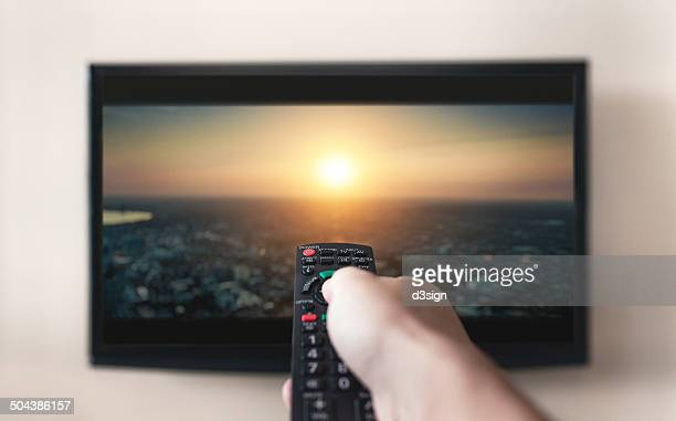 human holding remote control with movie channel - lcd tv stock photos and pictures