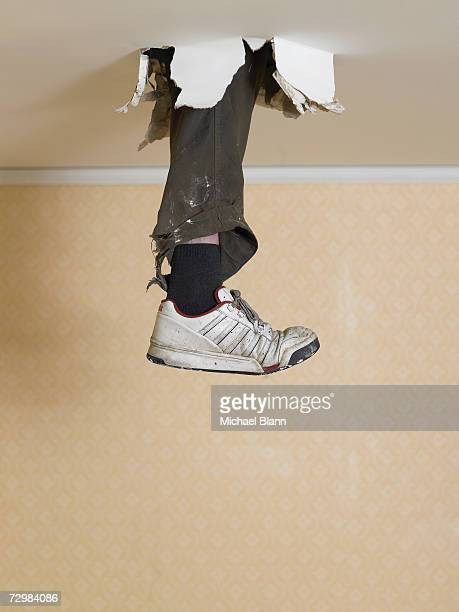Human leg dangling from hole in ceiling