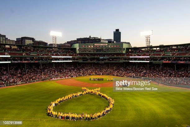A human ribbon of child cancer patients and their families is formed during a Go Gold For Cancer childhood cancer awareness pregame ceremony before a...