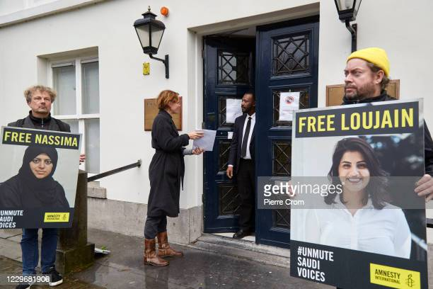 Human right activist of Amnesty International hands over a petition to a worker of the Saudi Arabia ambassy as human right activists demonstrate...