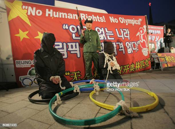 Human rights activists displaying Olympic rings on the ground stage an act depicting human rights abuses as they take part in a demonstration at the...