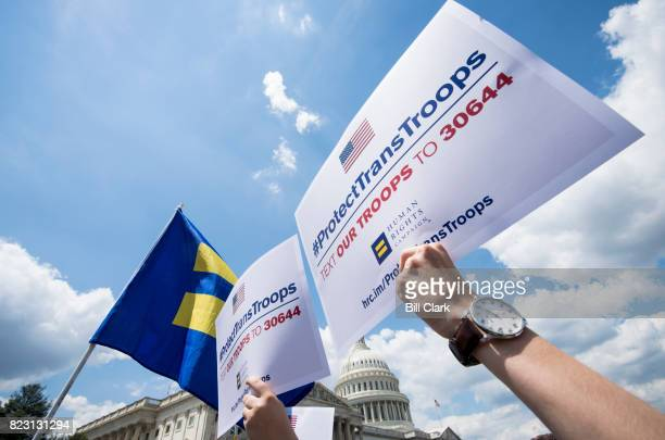 Human Rights Campaign supporters hold up signs as the House Democrats along with the LGBT Equality Caucus' Transgender Equality Task Force members...