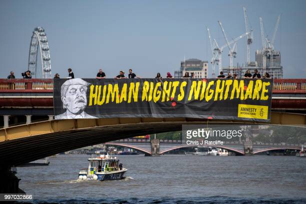 Human rights group Amnesty International drop a banner from Vauxhall Bridge opposite the US Embassy protesting against US President Donald Trump's...