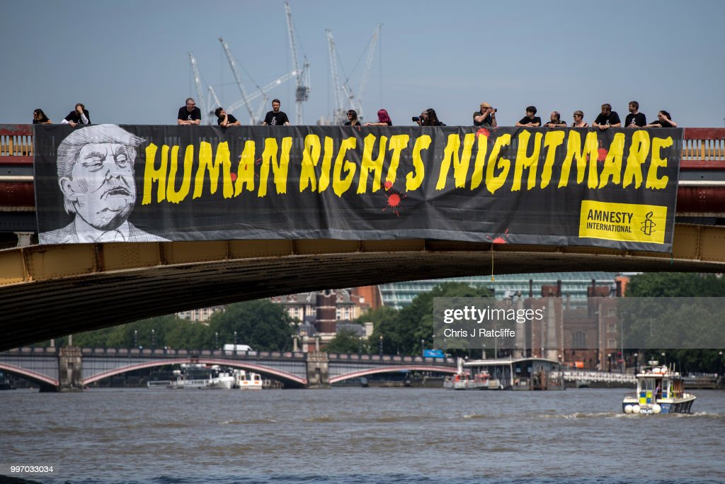 Human rights group Amnesty International drop a banner from Vauxhall Bridge opposite the US Embassy protesting against US President Donald Trump's visit to the United Kingdom on July 12, 2018 in London, United Kingdom. The President of the United States and First Lady, Melania Trump, have arrive in the United Kingdom for their first official visit. Whilst they are here they will have dinner at Blenheim Palace, visit Prime Minister Theresa May at Chequers and take tea with the Queen at Windsor Castle.