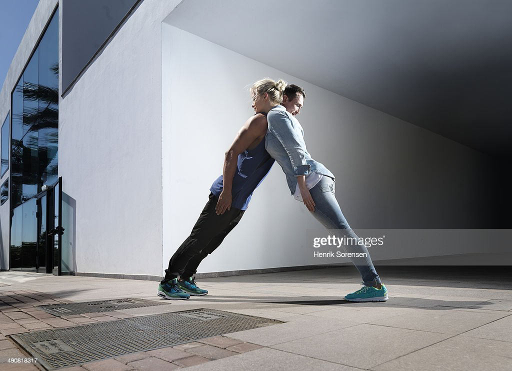 A man an a woman creating a human sculpture in an open urbane space.