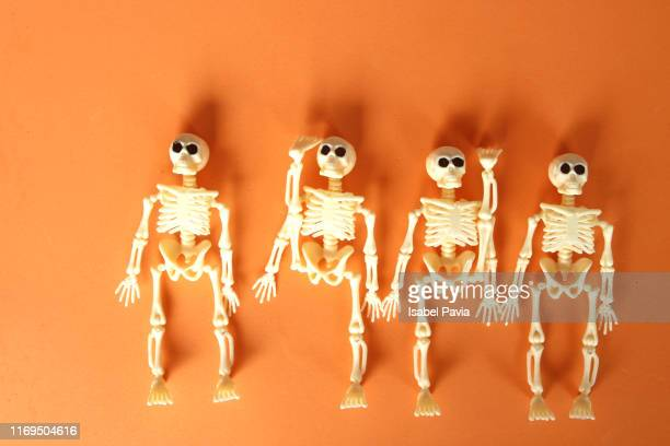 human skeletons on orange background. halloween concept - cartoon halloween stock photos and pictures