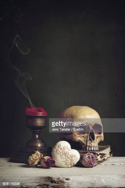 human skull and candle with flowers on table - human skull stock pictures, royalty-free photos & images