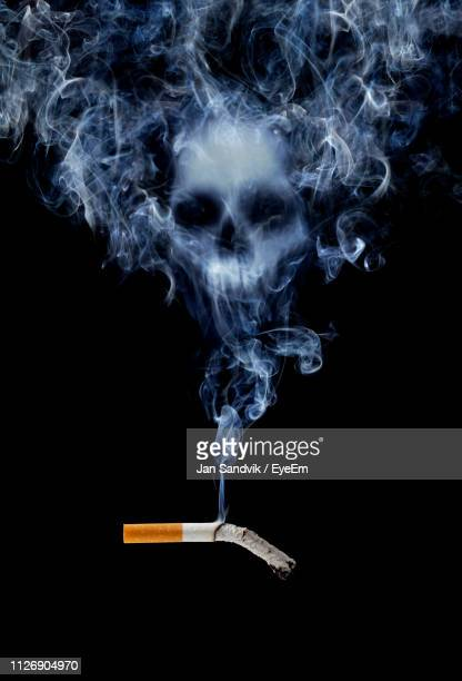 human skull made from cigarette smoke against black background - human skull stock pictures, royalty-free photos & images