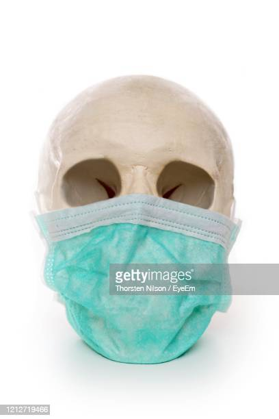 human skull wearing a protective mouth mask. dangerous influenza pandemic concept. - funny surgical mask stock pictures, royalty-free photos & images