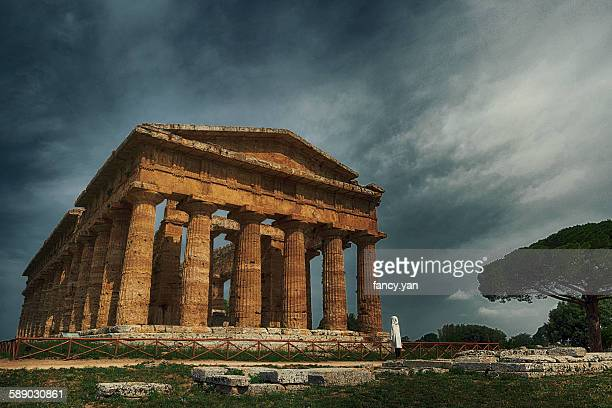 Human standing in front of ancient greek temple