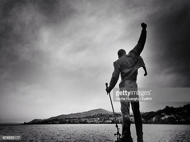 Human Statue In Lake Geneva Against Cloudy Sky