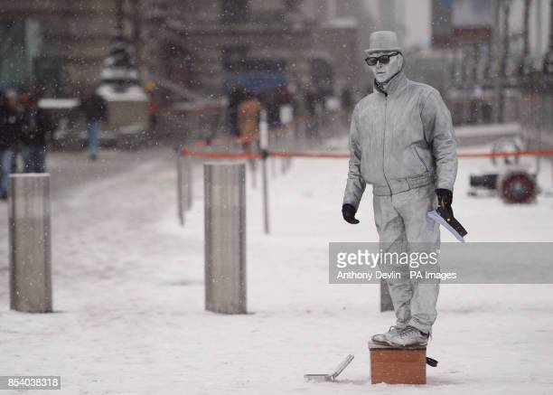 A human statue poses for the public as heavy snow falls in London
