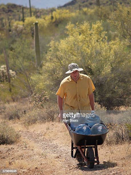 Humane Borders volunteer Michael Oerhrtmann carries water in 110 degree heat to one of the more than 50 sites Humane Borders services May 20 2005 in...