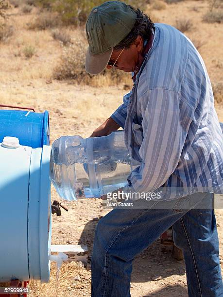 Humane Borders volunteer Roberto A Reveles adds water to one of the more than 50 emergency water stations the group has placed throughout the...