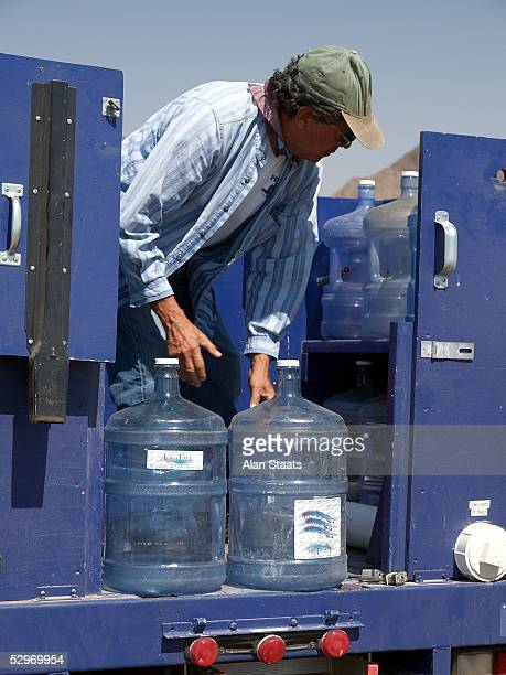 Humane Borders volunteer Roberto A Reveles prepares to bring water to one of the more than 50 emergency water stations the group has placed...