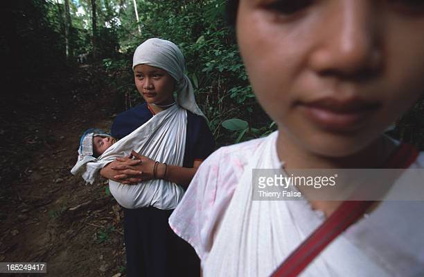 Humanitarian commando on a mission in Karen State A group of refugees on a path in the jungle walking towards Thailand
