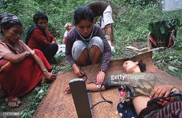 Humanitarian commandos Karen State Paw Htoo a 31yearold Karen nurse gives examinations on a wild grass field in a Burmese jungle