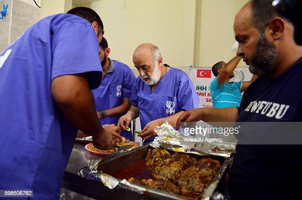 Humanitarian Relief Foundation Gaza Representative Mehmet Kaya prepare foods to distribute during the opening ceremony of a meal center to provide...