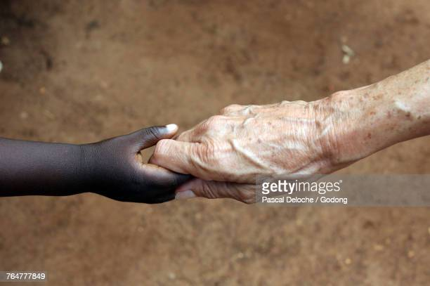 humanitarian worker holding childs hand. togo. - parrainage photos et images de collection