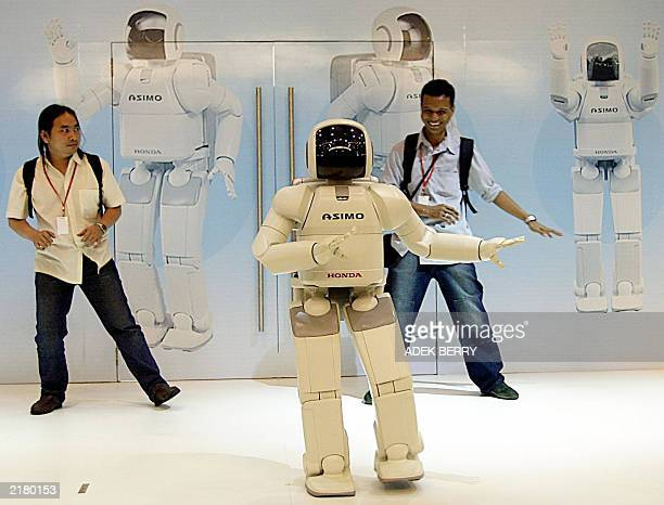 A humanoid robot ASIMO performs a Indonesian traditional dance 'Pocopoco' with two men in a motor show in Jakarta 18 July 2003 ASIMO released by...