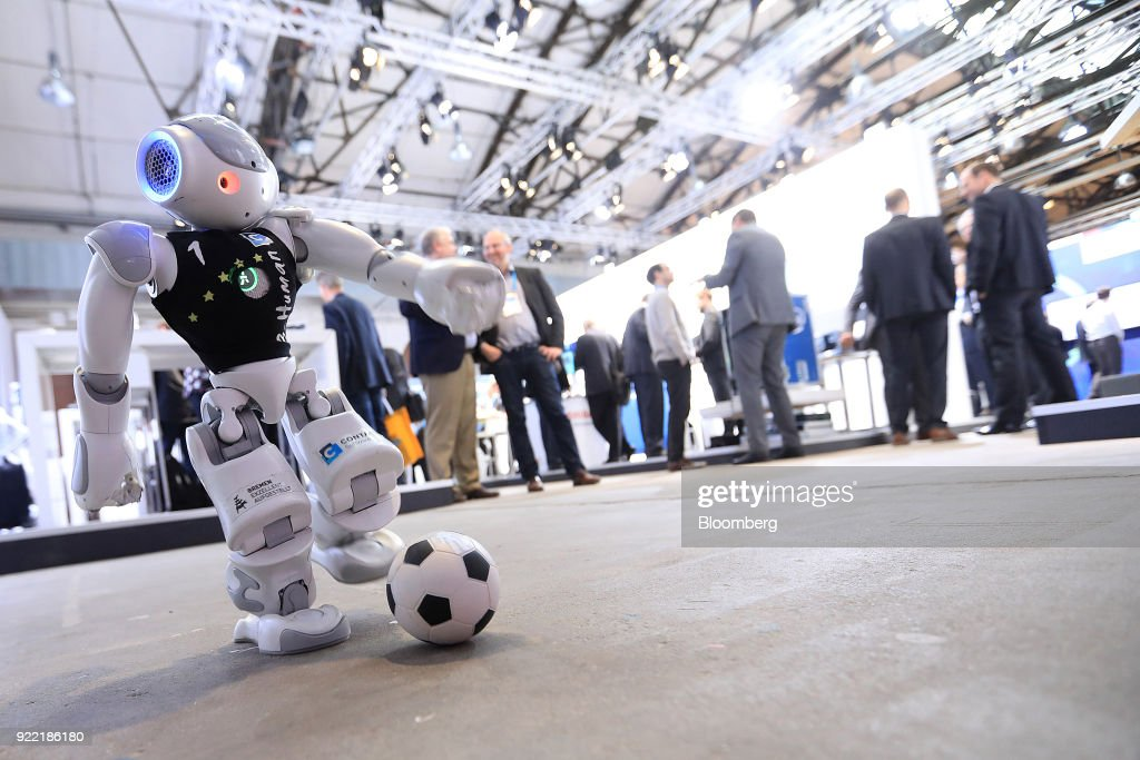 A humanoid robot plays soccer in the Contact Software GmbH exhibition area at the Robert Bosch GmbH Internet of Things (IoT) conference in Berlin, Germany, on Wednesday, Feb. 21, 2018. Bosch raked in record profit and revenue last year and foresees more growth in 2018 even as the German auto-parts giant wrestles with weakness in the scandal-beset diesel segment that might be compounded by controversial air-quality tests on monkeys. Photographer: Krisztian Bocsi/Bloomberg via Getty Images