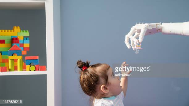 humanoid robotic hand giving pacifier to baby - robot arm stock pictures, royalty-free photos & images