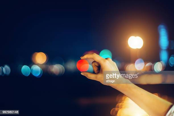 human's hand catching the bokeh of city street light in the dark - hands circle stock pictures, royalty-free photos & images