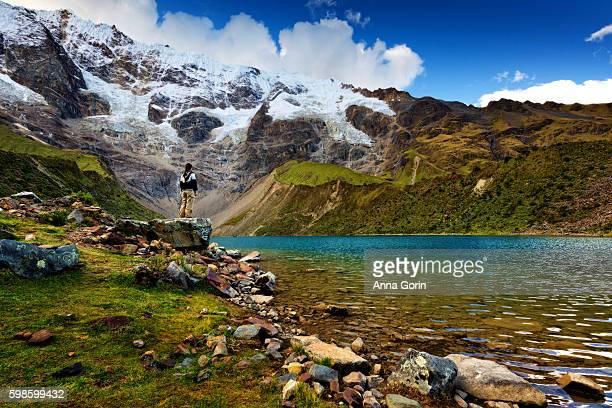 humantay lake along salkantay trek to machu picchu, peru, with female tourist looking at view - provinz cusco stock-fotos und bilder