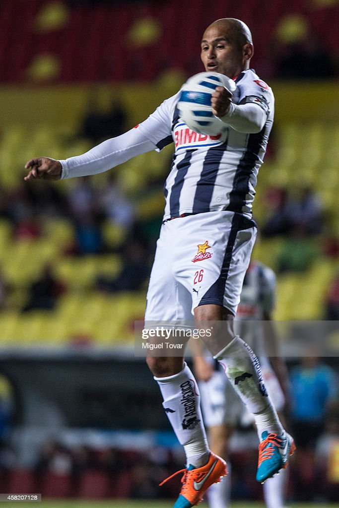 Humberto Suazo of Monterrey jumps to get down the ball with his chest during a match between Morelia and Monterrey as part of 15th round Apertura 2014 Liga MX at Jose Maria Morelos y Pavon Stadium on October 31, 2014 in Morelia, Mexico.