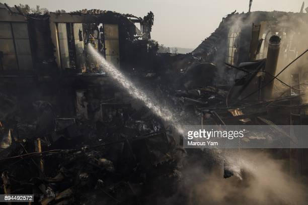 Humboldt County firefighter Jimmy McHaffie right sprays down smoldering fire underneath the rubble of a home that was destroyed by the Thomas Fire on...