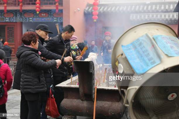 A humidifier emits vapour as worshippers light incense to pray for happiness and good health at the City God Temple on February 17 2018 in Zhengzhou...