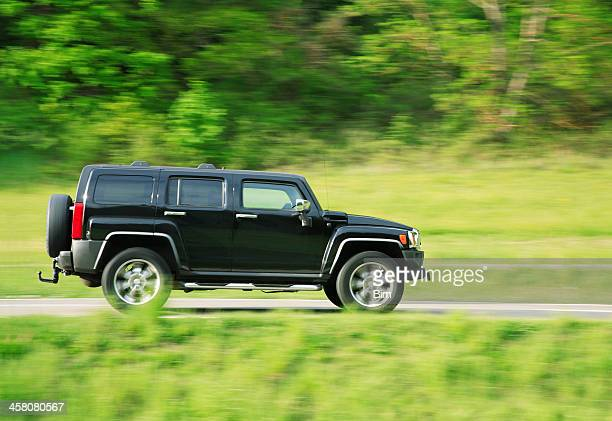 hummer h3 driving on country road in spring - hummer stock photos and pictures