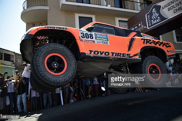 Hummer's driver US Robby Gordon and codriver Johnny Campbell jump on the podium at the end of the 2015 Dakar Rally stage 6 between Antofogasta and...