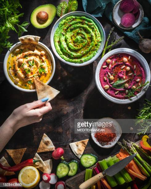 hummus bowls of chickpeas, avocado and beetroot female hand dip with cut vegetables for dipping - lebanon country stock pictures, royalty-free photos & images