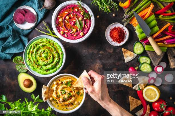 hummus bowls of chickpeas, avocado and beetroot male hand dip with cut vegetables for dipping - lebanon country stock pictures, royalty-free photos & images